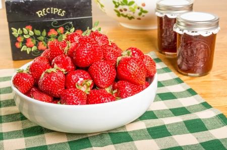 Kom met verse aardbeien met potten jam of gelei