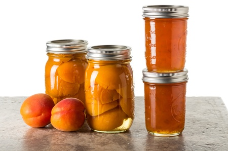 Fresh apricots preserved as homemade jam and in mason jars photo