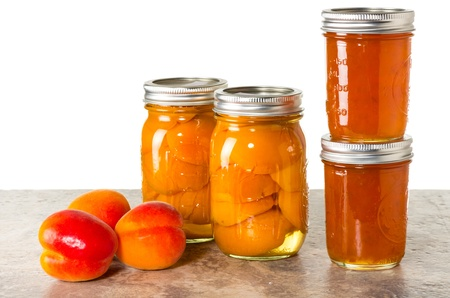 preserving: Fresh apricots preserved as homemade jam and in mason jars Stock Photo