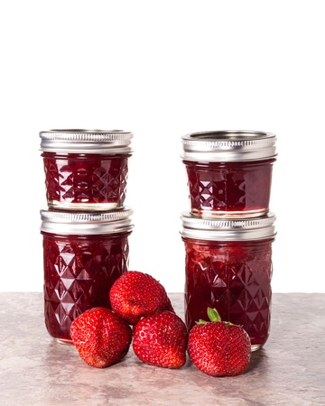 Fresh strawberries preserved in jars as homemade jam and jelly photo