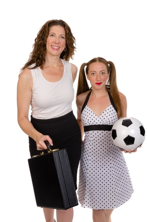 sports attire: A smiling business woman with briefcase and daughter with soccer ball Stock Photo