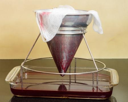 Filteren van verse aardbeien door de kaasdoek om gelei te maken