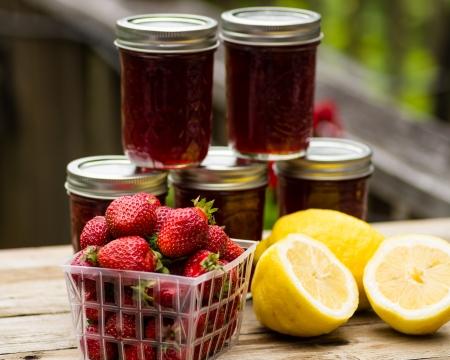 Verse zelfgemaakte Strawberry lemon curd jam of domeinen met aardbeien en citroenen
