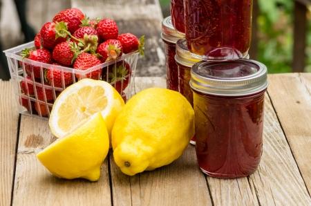 Verse zelfgemaakte aardbei lemon curd jam of domeinen met aardbeien en citroenen