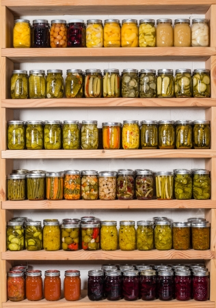 Storage shelves in pantry with homemade canned preserved fruits and vegetables photo