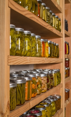 Canned goods on wooden storage shelves in pantry photo