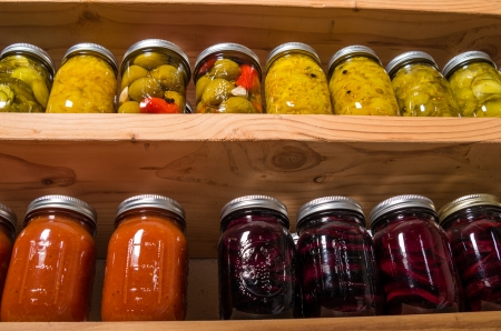 Canned goods on wooden storage shelves in pantry Banco de Imagens