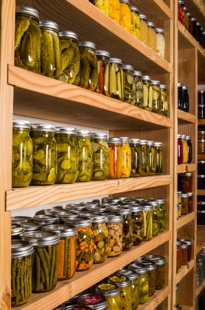 Canned goods on wooden storage shelves in pantry Stock Photo