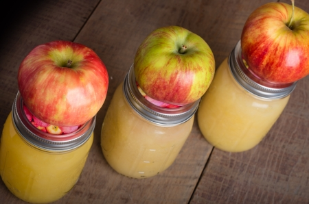 Jars of canned applesauce with fresh apples