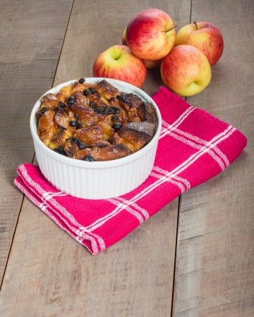 Apple bread pudding with raisins baked in white bowl