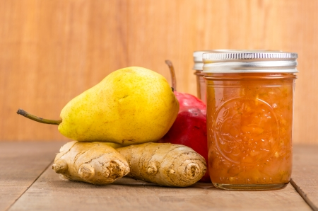 Pear ginger jam in mason jars with red and yellow pears