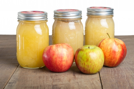 Jars of fresh apple sauce with red apples