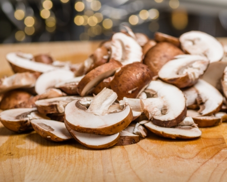 Fresh sliced mushrooms on a wooden cutting board in kitchen Фото со стока