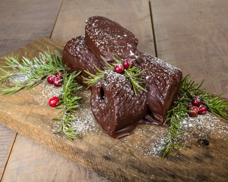 yule log: Chocolate Yule log with green branches and cranberries