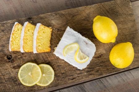 lemon cake: Sliced lemon pound cake with white icing and lemons Stock Photo