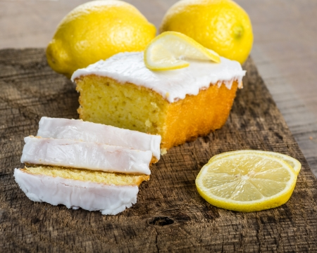 Sliced lemon pound cake with white icing and lemons Stock Photo