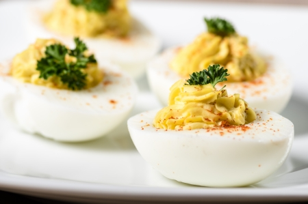 piped: Piped and filled deviled eggs garnished with parsley and paprika Stock Photo