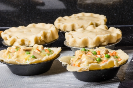 A group of turkey pot pies being prepared for baking Banco de Imagens