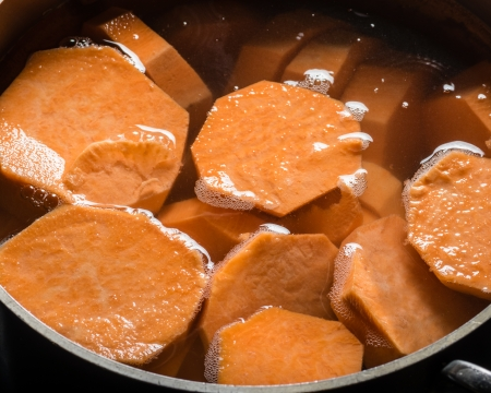 boiling: Orange sweet potatoes in a sauce pan being cooked for dinner