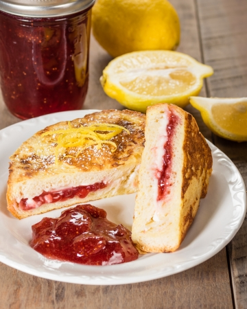 Breakfast of stuffed French toast with strawberry and cream cheese filling lemons and jam