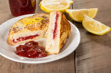 Breakfast of stuffed French toast with strawberry and cream cheese filling with lemon slices