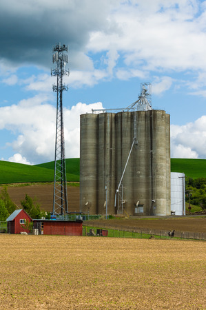 grainery: A large grain silo storage building with a cell phone tower Stock Photo