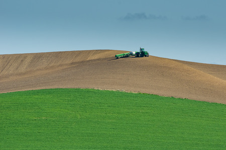 A tractor and planter working to farm an agricultural area Stock Photo
