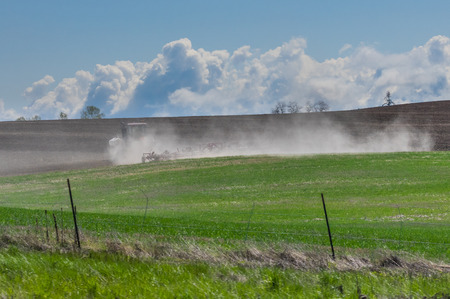 A tractor and harrow raise a dust cloud as they cultivate a field