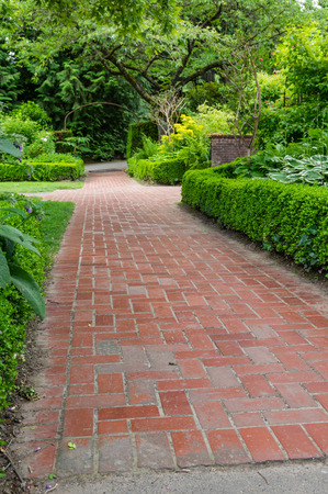planted: Brick pathways and hedge inside a large planted garden Stock Photo