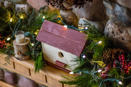 mantel: A wooden mantel decorated with greens and a wooden bird house Stock Photo