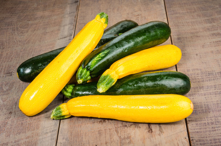 Zucchini and yellow squash displayed on a wooden table Stock Photo