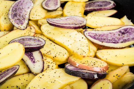 fingerling: Blue and yellow potatoes sliced in a cast iron skillet Stock Photo