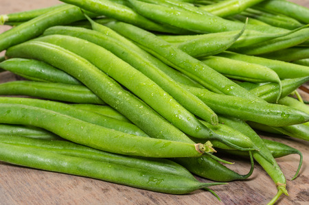 long bean: Freshly picked green or snap beans on a wooden table Stock Photo