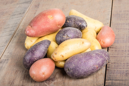 fingerling: Group of fresh fingerling potatoes on a wooden table Stock Photo