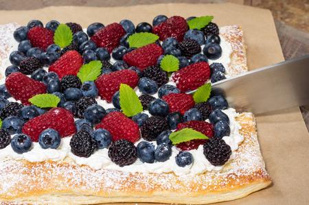 Homemade berry tart with knife cutting Reklamní fotografie
