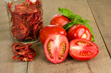 Fresh red tomatoes and basil with jar of dried tomatoes Stockfoto