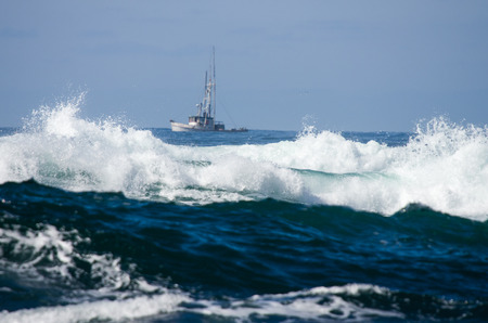 pacific ocean: A small fishing boat is navigating just outside the surf Stock Photo