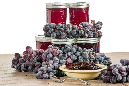 Bowl of fresh grape jelly with grapes and jars isolated