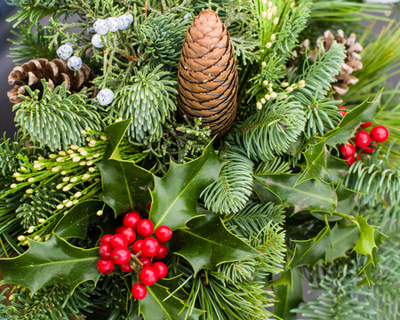 Mixed evergreen arrangement including pine cones holly and cedar