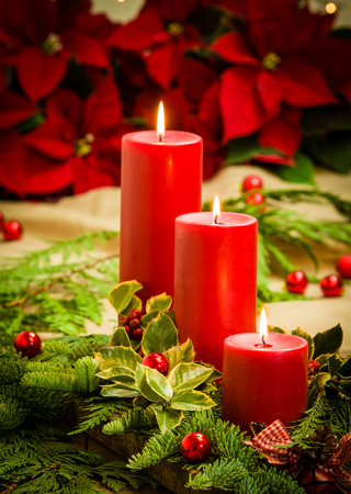 Christmas centerpiece with lit candles and poinsettias