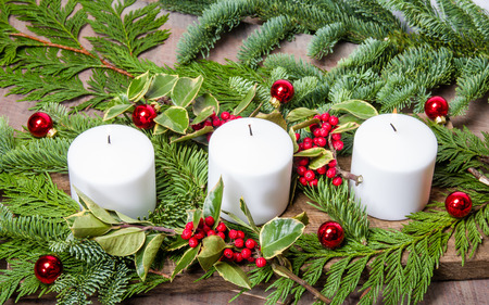an evergreen christmas centerpiece with three white candles and holly stock photo 34163011 - An Evergreen Christmas