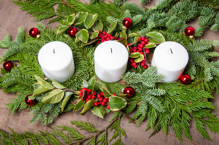 an evergreen christmas centerpiece with three white candles and variegated holly stock photo 34163353 - An Evergreen Christmas