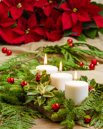 Lit candles in an evergreen centerpiece and poinsettias with glow effect photo