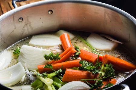 A large stock pot on a stove with vegetables cut for making soup Banco de Imagens