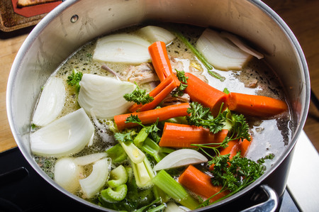 broth: A large stock pot on a stove with vegetables cut for making soup Stock Photo