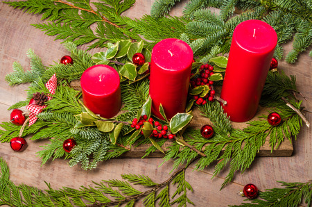 Three red candles in a Christmas decorative centerpiece