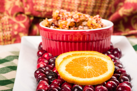 Fresh cranberries on plate with bowl and orange slices