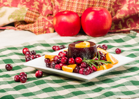 Fresh cranberry sauce on plate with red apples