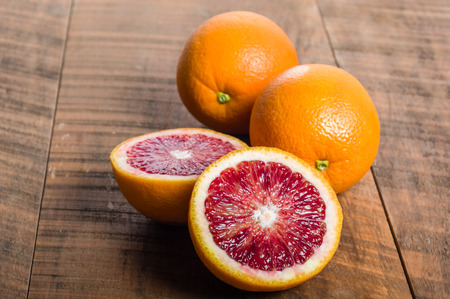 Blood oranges citrus fruit on table with cut half showing interior