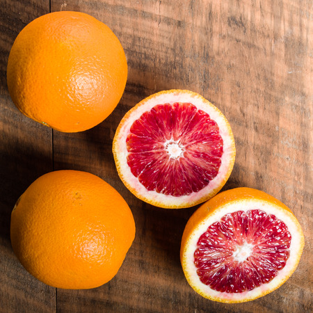 cut: Blood oranges citrus fruit on table with cut half showing interior